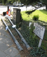 Remains of traffic signal poles on pavement in Station Road with 'consultation' notices still attached
